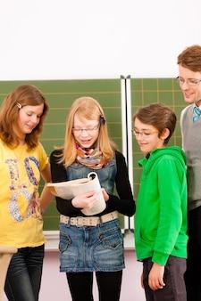 Uczniowie z nauczycielem na tablicy w szkole