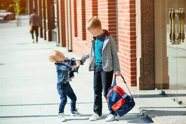 Uczniowie z plecakiem idą do szkoły. stylowi bracia na zewnątrz. szkoła podstawowa.