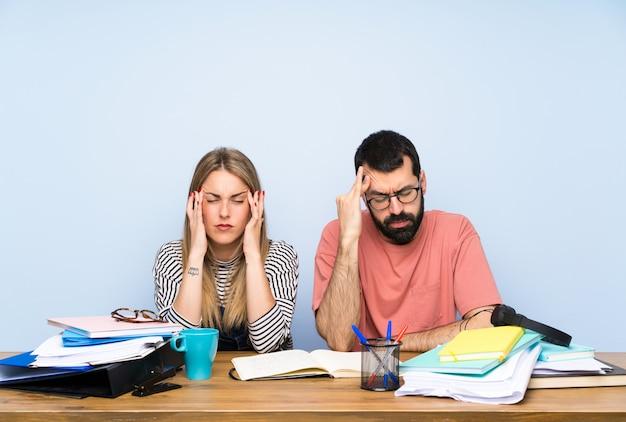 Uczniowie z wieloma książkami z bólem głowy