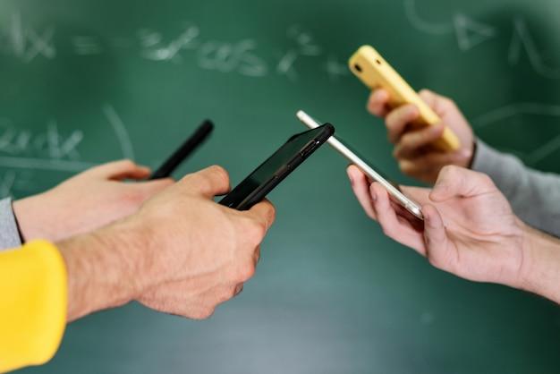 Uczniowie za pomocą telefonów komórkowych w klasie na tablicy