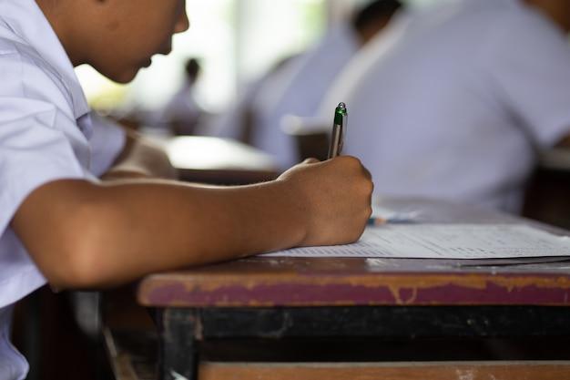 Uczniowie zdający egzamin ze stresem w klasie szkolnej