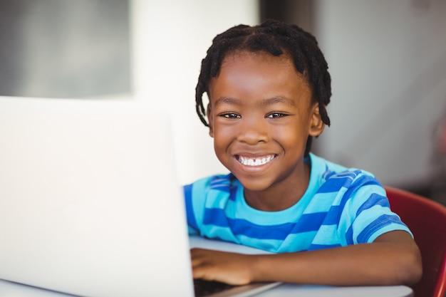 Uczniowski obsiadanie na krześle i używać laptopie w szkole