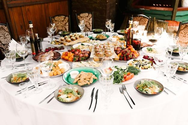 Uczta przy okrągłym stole pełna pysznych potraw i przekąsek, piękna oprawa, catering, wakacje na świeżym powietrzu