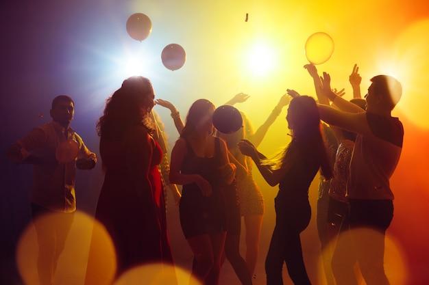 Uczucia tłum ludzi w sylwetce podnosi ręce na parkiecie na neonowym świetle