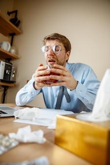 Uczucie mdłości i zmęczenia. człowiek z filiżanką gorącej herbaty pracuje w biurze