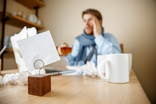 Uczucie mdłości i zmęczenia. sfrustrowany młody człowiek masuje głowę siedząc przy swoim miejscu pracy