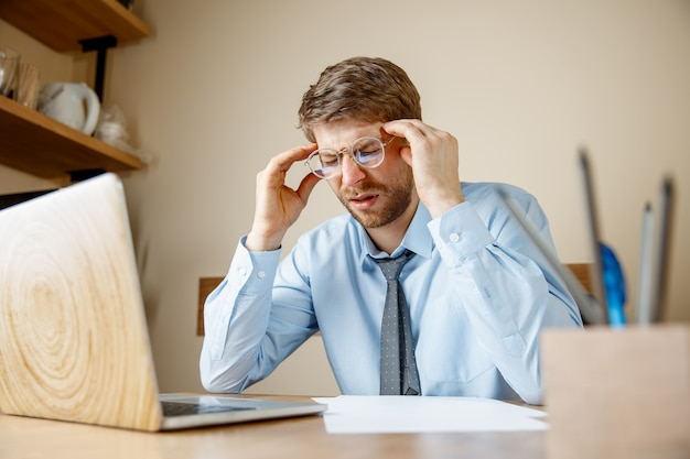 Uczucie mdłości i zmęczenia. sfrustrowany smutny nieszczęśliwy chory młody człowiek masuje głowę, siedząc w swoim miejscu pracy w biurze.