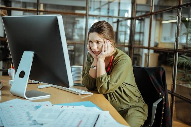Uczucie przeciążenia. ciemnowłosa bizneswoman nosząca ładny czerwony naszyjnik czuje się przeciążona