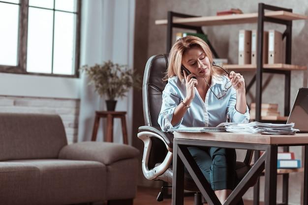 Uczucie przeciążenia. zajęta atrakcyjna doświadczona bizneswoman czuje się przeciążona ważną pracą