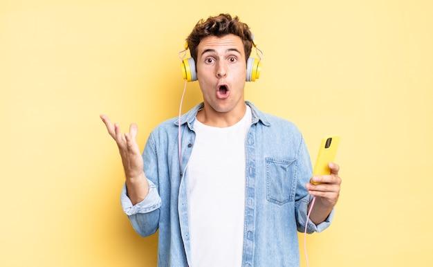 Uczucie skrajnego szoku i zaskoczenia, niepokoju i paniki, zestresowanego i przerażonego spojrzenia. koncepcja słuchawek i smartfona