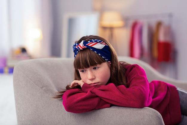 Uczucie smutku. atrakcyjna nastolatka siedzi na kanapie, opierając się na ramionach