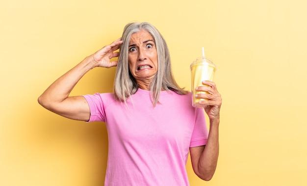 Uczucie stresu, zmartwienia, niepokoju lub strachu, z rękami na głowie, panika z powodu błędu i trzymanie koktajlu mlecznego