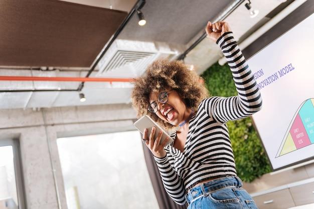 Uczucie szczęścia. piękna młoda kobieta wyrażająca pozytywne nastawienie, trzymając telefon w prawej ręce