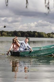Uczucie zabawy. piękna młoda para korzystających romantyczną randkę podczas wiosłowania łodzi.