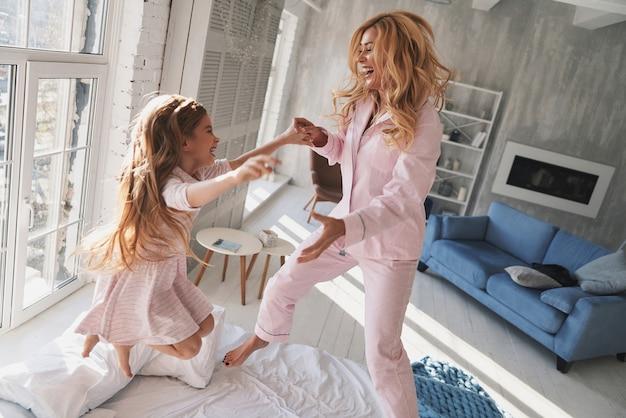 Uczucie zabawy. widok z góry uroczej małej dziewczynki skaczącej na łóżku z matką podczas spędzania czasu w domu