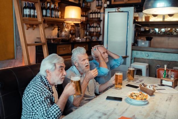 Uczucie zakłopotania. trzech przyjaciół czuje się zakłopotanych podczas oglądania piłki nożnej w pubie