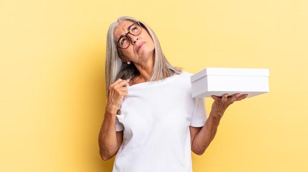 Uczucie zestresowania, niepokoju, zmęczenia i frustracji, ciągnięcie za koszulkę, wyglądanie na sfrustrowanego problemem i trzymanie białego pudełka