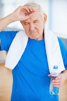 Uczucie zmęczenia po treningu sportowym. zmęczony starszy mężczyzna z ręcznikiem na ramionach, trzymający zamknięte oczy i dotykający czoła podczas stania w klubie fitness