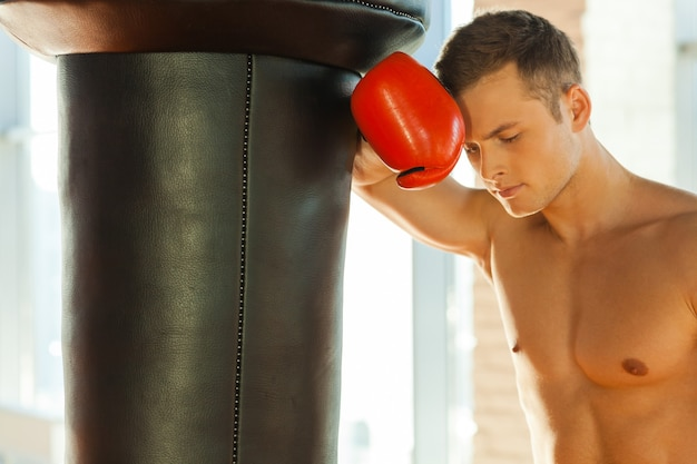 Uczucie zmęczenia po treningu. zmęczony młody bokser w sportowych rękawiczkach oparty o worek treningowy