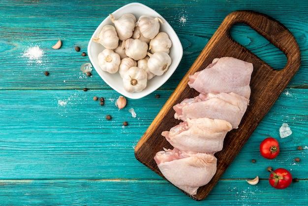Uda z kurczaka surowego na niebieskim tle drewnianych.