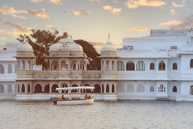 Udaipur, indie - 19 stycznia 2020: taj lake palace nad jeziorem pichola o wschodzie słońca w udaipur, rajasthan, indie.