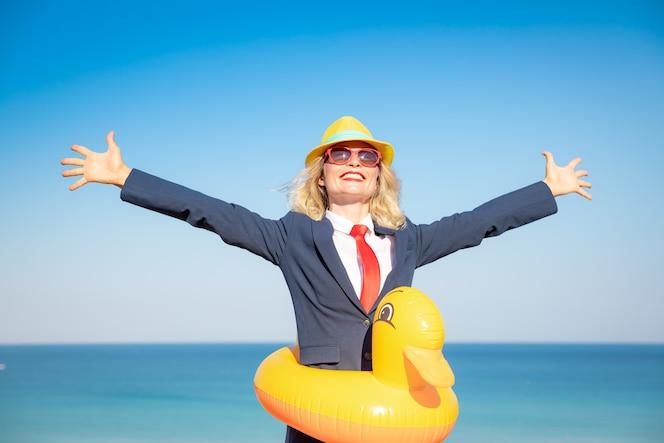 Udana bizneswoman bawi się na plaży młoda kobieta na tle morza i nieba