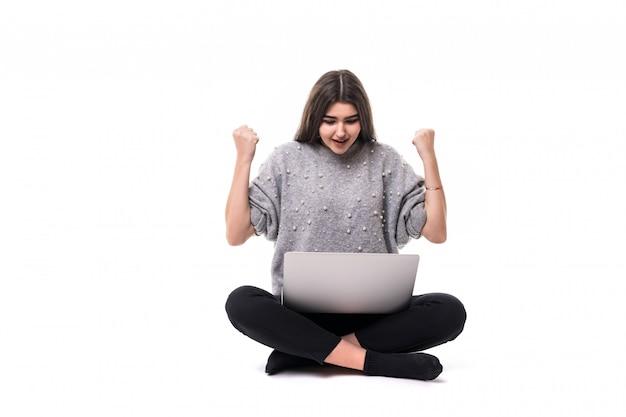Udana brunetka modelka w szarym swetrze siedzi na podłodze i pracuje nad swoim laptopem