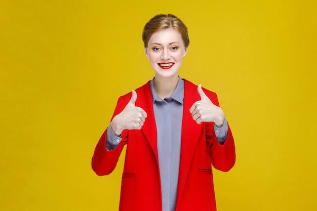 Udana czerwona głowa bizneswoman w czerwonym garniturze pokazującym jak znak