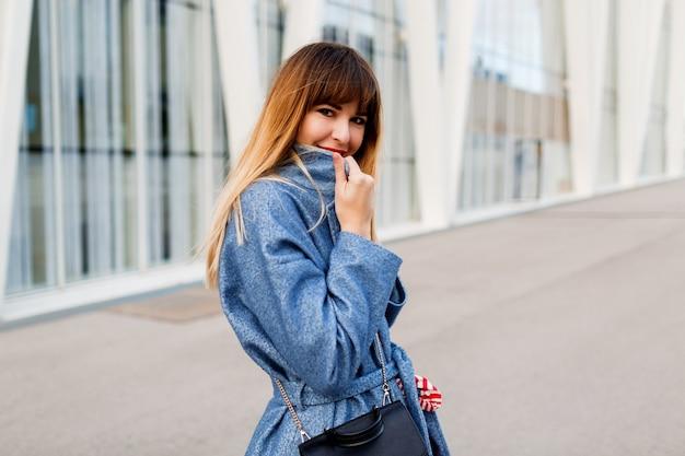 Udana kobieta pozuje w pobliżu nowoczesnego centrum biznesowego w płaszcz z wełny niebieski
