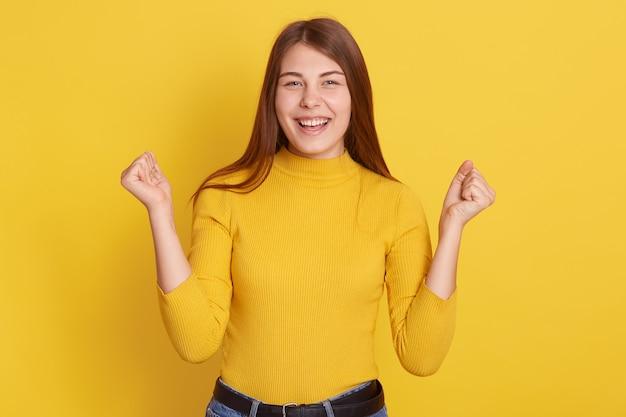 Udana kobieta świętuje z podniesionymi pięściami na żółto