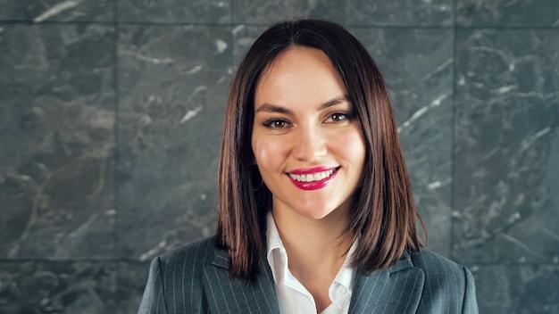 Udana kobieta z czerwoną szminką uśmiecha się do kamery przed szarą marmurową ścianą z białymi wzorami w pobliżu biura
