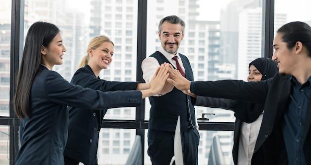 Udana koncepcja biznesowa pracy zespołowej, liderzy i pracownicy biurowi łączą siły, aby odnieść sukces jako zespół małej firmy w sali konferencyjnej ze szczęśliwym uśmiechem i nowoczesnym tłem miasta.