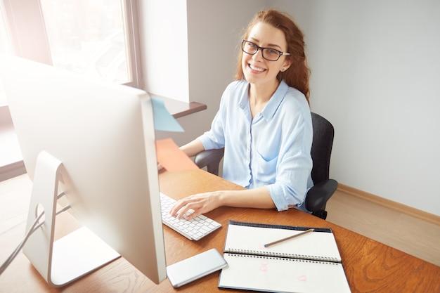 Udana ładna bizneswoman pracuje na komputerze w biurze
