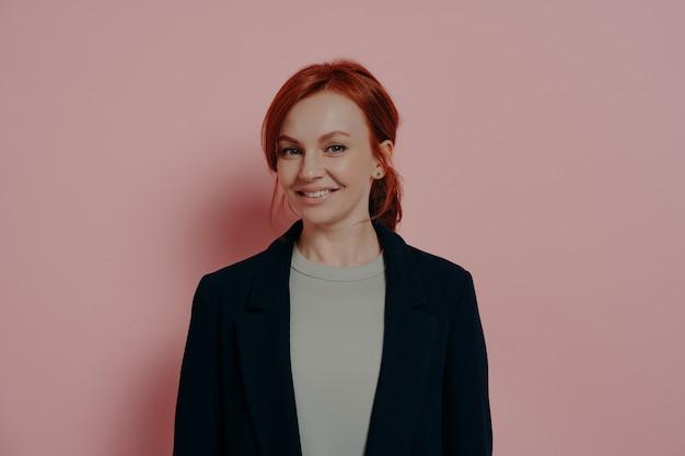 Udana ładna rudowłosa kobieta patrząca na kamerę z pewnością siebie i przyjemnym uśmiechem, stojąca odizolowana na różowym tle w studio, stylowa ruda modelka w swobodnym stroju uśmiechnięta radośnie