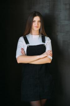 Udana młoda dama. piękna brunetka dziewczyna stojąca z założonymi rękoma