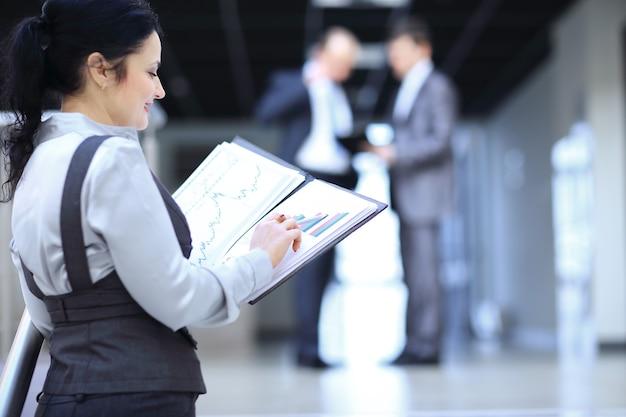 Udana młoda kobieta biznesu na niewyraźnym biurze w tle