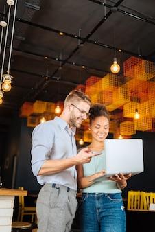 Udana para. stylowa para, która odniosła sukces, korzysta z laptopa podczas ciężkiej pracy we własnej restauracji