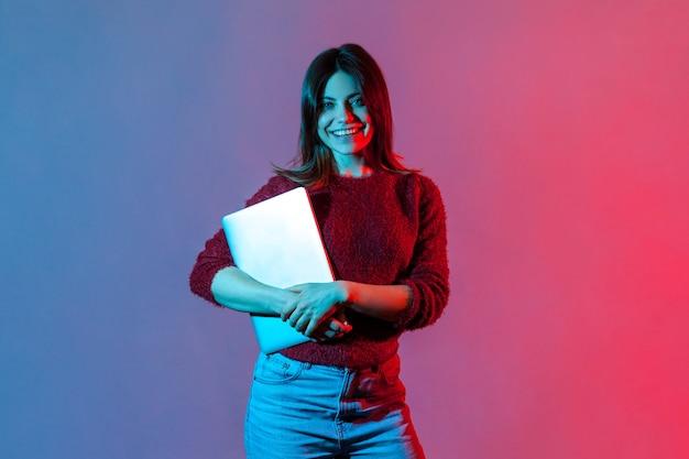 Udana pewna siebie pracownik biurowy dziewczyna w swobodnym swetrze stojąca, trzymająca zamkniętego laptopa