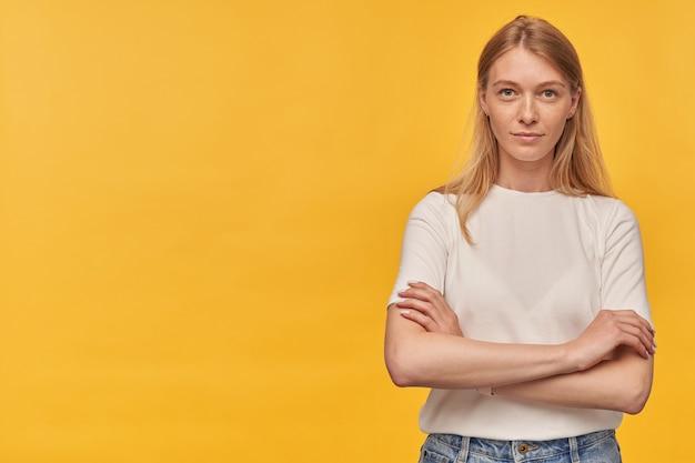 Udana piękna kobieta z piegami w białej koszulce, stojąca z założonymi rękami i wygląda pewnie na żółto