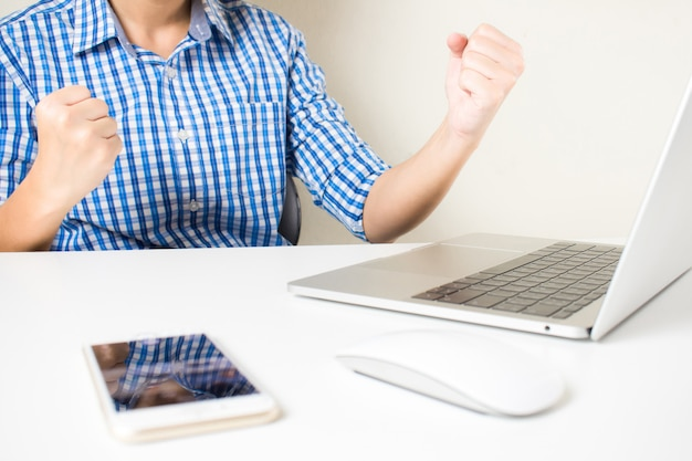 Udana praca biznesmenów. młodzi biznesmeni, którzy są szczęśliwi, gdy otrzymują dobre wiadomości w laptopach.