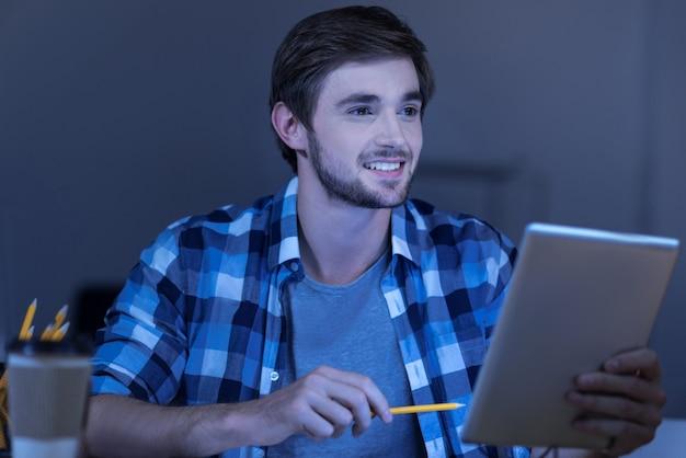 Udana praca. wesoły miły młody człowiek trzyma tablet i uśmiecha się, będąc zadowolony ze swojej pracy