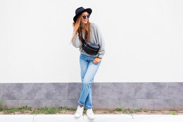 Udana stylowa dziewczyna z szczerym uśmiechem pozuje na białej ścianie miejskiej