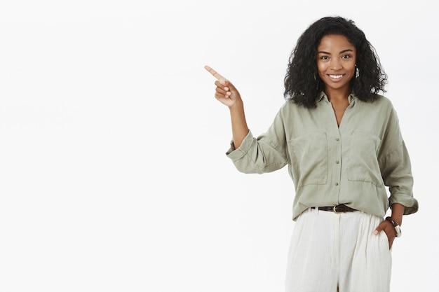 Udana stylowa i szczęśliwa ciemnoskóra kobieta prezentuje projekt w pobliżu boćwiny trzymając rękę w kieszeni wskazującą w lewo i uśmiechając się zachwycona