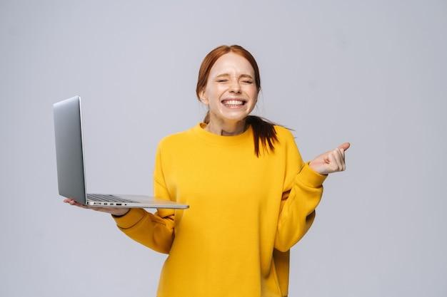 Udana, szczęśliwa, zszokowana młoda kobieta z zamkniętymi oczami, trzymająca laptopa