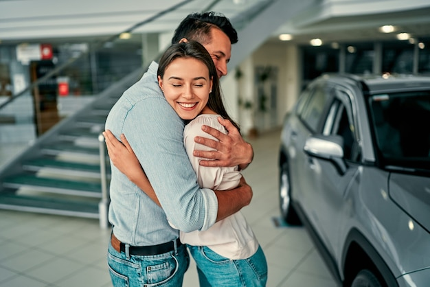 Udana wizyta w salonie. szczęśliwa młoda para szczęśliwy uścisk, który wybiera i kupuje nowy samochód dla rodziny.