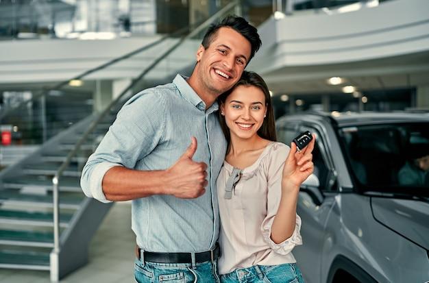 Udana wizyta w salonie. szczęśliwa młoda para wybiera i kupuje nowy samochód dla rodziny.