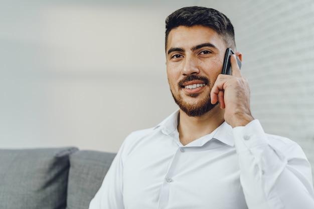 Udane młody biznesmen rozmawia przez telefon, portret