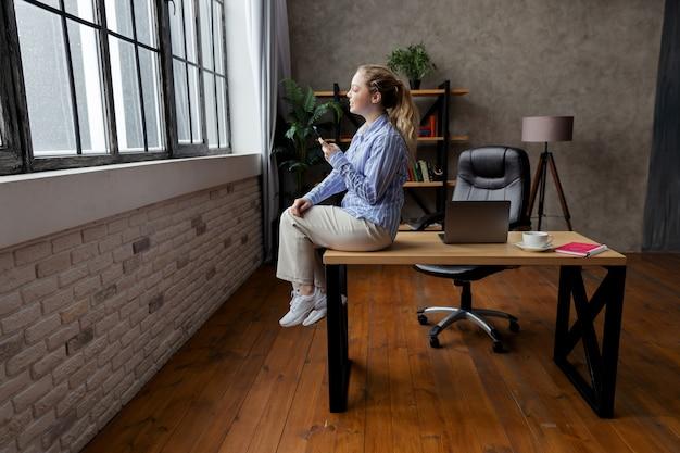 Udane młody bizneswoman trzymać telefon, siedząc na biurku i patrząc w okno. wysokiej jakości zdjęcie