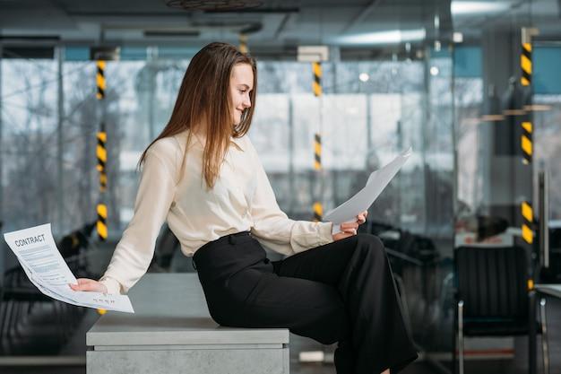 Udane negocjacje. miejsce pracy prawnika korporacyjnego. uśmiechnięta biznesowa kobieta siedzi na biurku czytanie kontraktu.