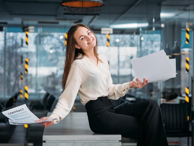 Udane negocjacje. miejsce pracy prawnika korporacyjnego. uśmiechnięta biznesowa kobieta siedzi na biurku z umową.